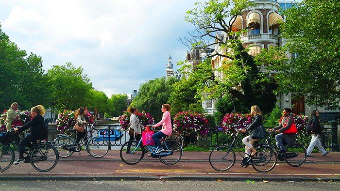 Diversos ciclistas pedalando na ciclovia em Amsterdã