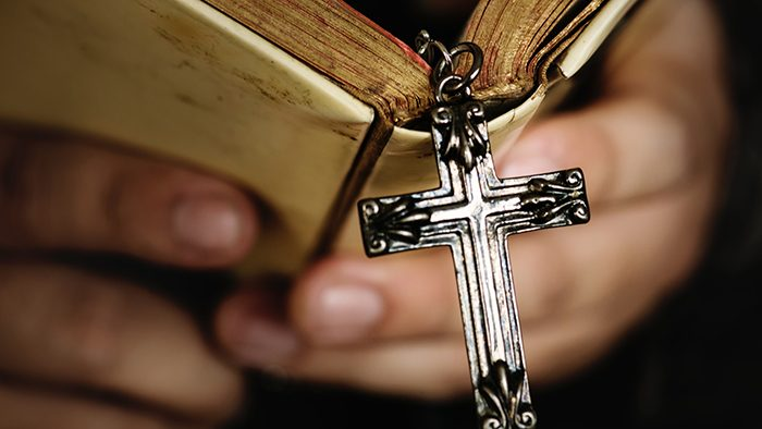 Mãos segurando um livro com crucifixo de metal