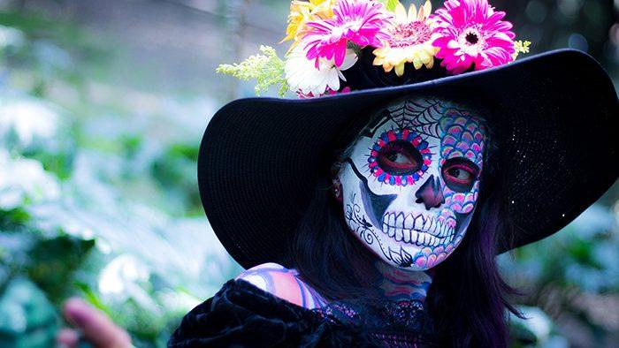 Mulher com chapéu e o rosto pintado de caveira mexicana em homenagem ao dia dos mortos