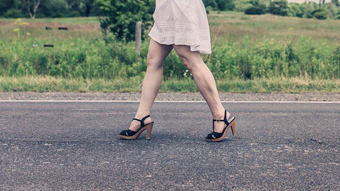 Mulher de salto alto andando no asfalto